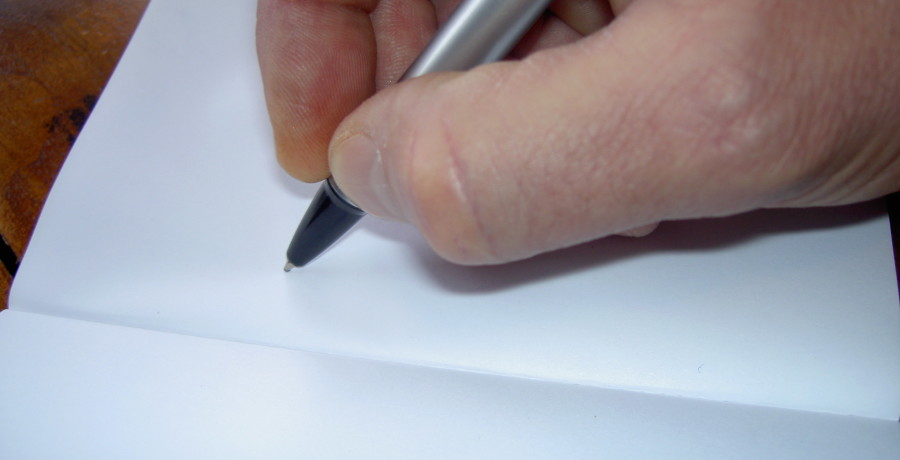 Image of person writing in food journal
